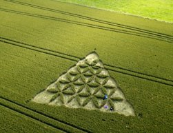 Crop circle experts have discovered a new formation - which is thought to resemble Westminster Abbey. The extraordinary design appeared at the weekend in Stanton St Bernard, Wilts...And its church-like spires have been likened to the famous landmark where the Duke and Duchess of Cambridge were married last year. SEE OUR COPY FOR DETAILS...Pictured: The other crop circle of triangular design, which is decorated with an intricate floral pattern, lies close to ancient Silbury Hill, the largest man-made mound in Europe...Please byline: Lucy Pringle/Solent News..© Lucy Pringle/Solent News & Photo Agency.UK +44 (0) 2380 458800.